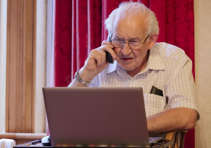 Old elderly senior man on phone at laptop computer at risk to cyber attack and online bank fraud stock image