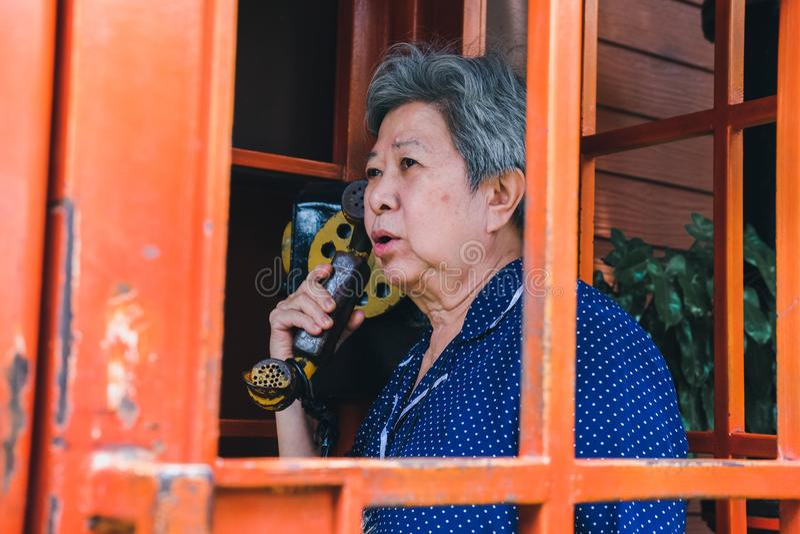 Old elderly senior woman talking on vintage public telephone stock photography