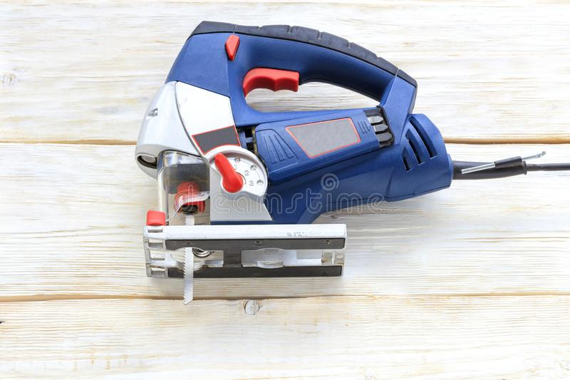 Old electric saw lying on a white wooden table after work. An old professional electric saw of blue color lies on a white wooden table stock image