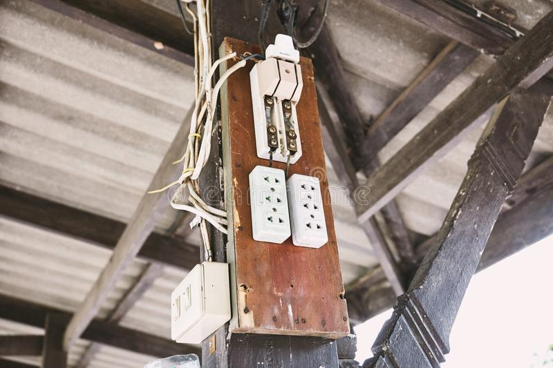 Old electric switching power breaker and AC outlet plugs on the wood board. The wooden board on the poll with AC switching power breaker with electric outlet royalty free stock image