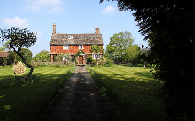 Old Elizabethan house. A 16th century timber-framed beamed house in a rural Sussex village in England. This farmhouse is a Grade II listed building with royalty free stock image
