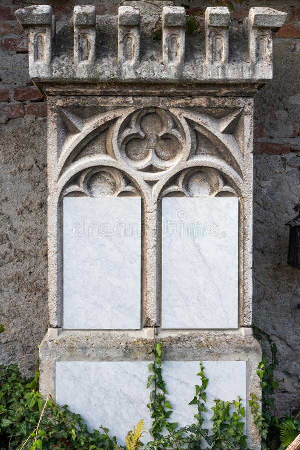 Old empty marble headstone board framed by arched sculpture. In cemetery. Originally blank, little post-processing royalty free stock image