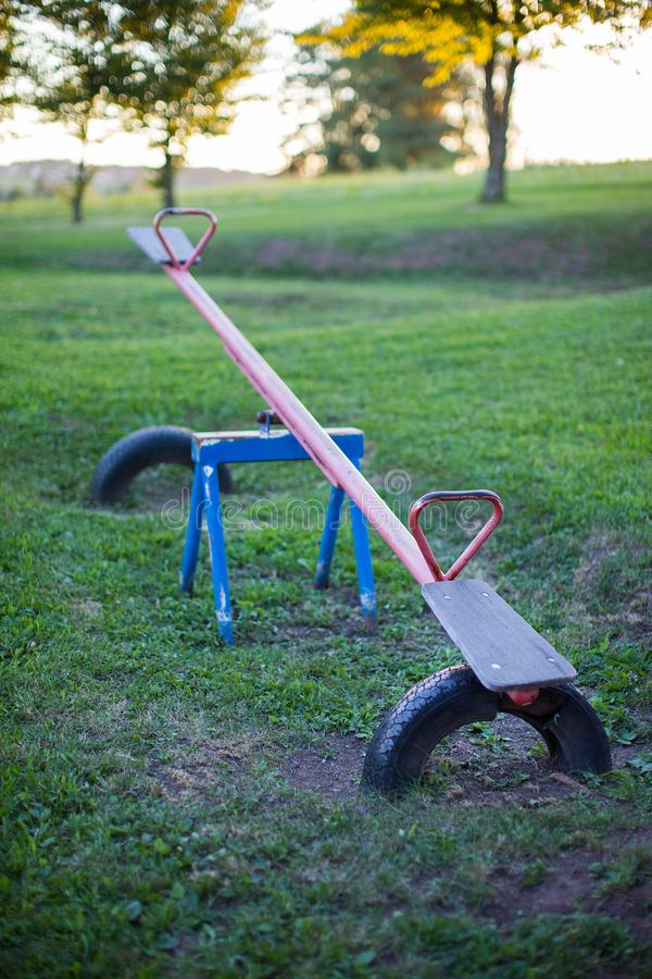 Old empty metal seesaw in an outdoor children`s playground. Old rusty empty metal seesaw in an outdoor children playground stock images