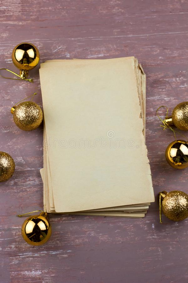 Old empty paper sheets with christmas golden balls. Top view brown shabby background stock image