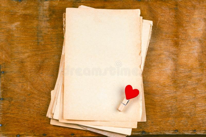 Old empty paper sheets and cloth pins with hearts top view wooden table mock up. For st valentines day card royalty free stock photography