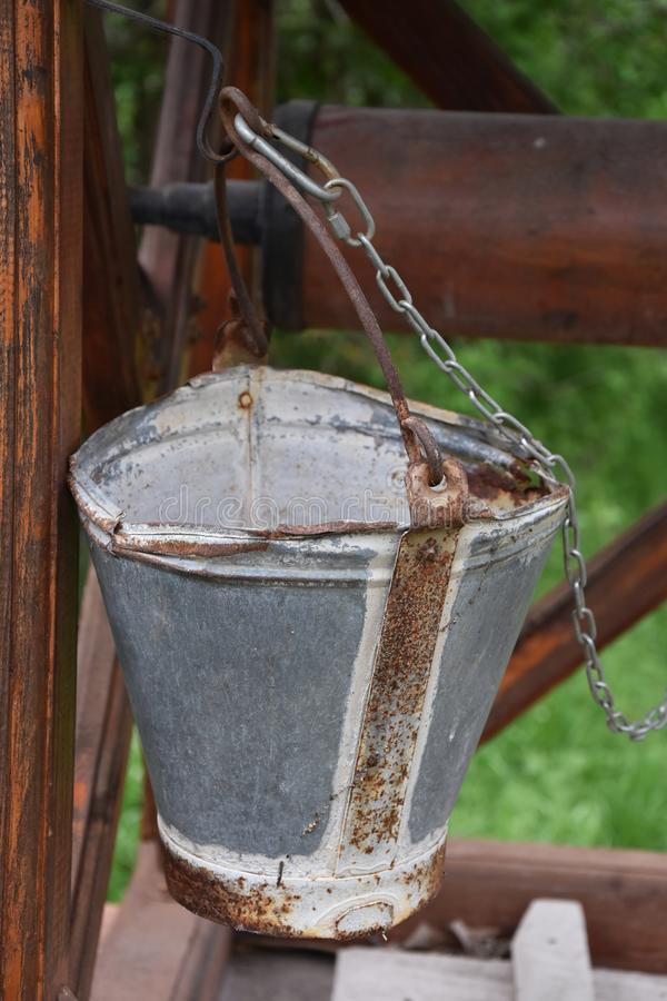 Empty steel bucket standing upright on a closed well. Old empty steel bucket standing upright on a closed well, closeup royalty free stock image