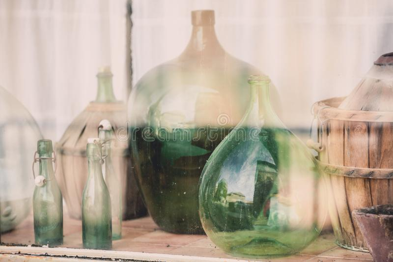 Old empty wine bottles behind the glass stock photo