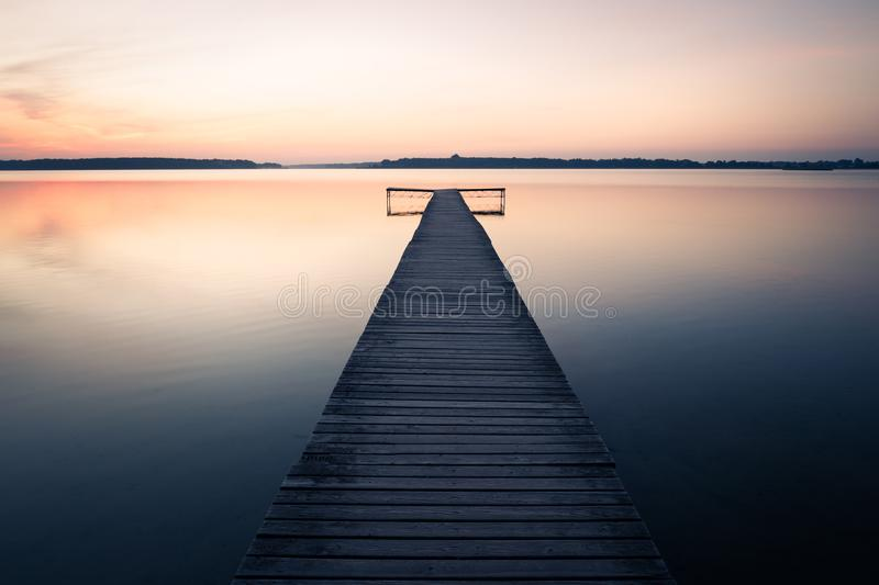 Empty wooden jetty on lake. Old empty wooden jetty on lake, during sunrise royalty free stock photo
