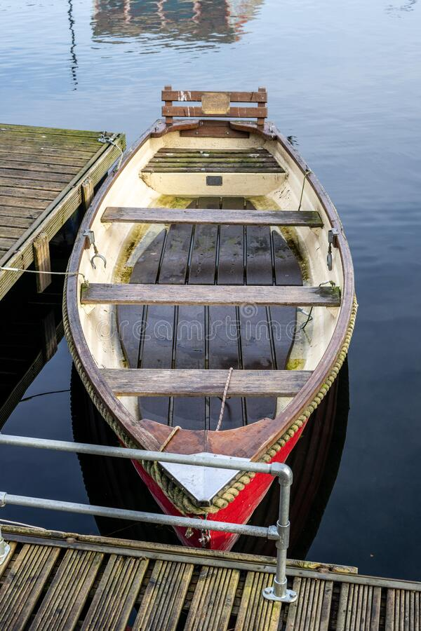 An old empty wooden rowing boat tied up on a wooden jetty on calm water royalty free stock photography