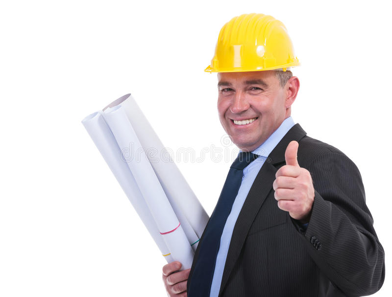 Old engineer holds drafts and thumbs up. Senior engineer holding some blueprints and showing thumb up while smiling to the camera. isolated on white background stock images