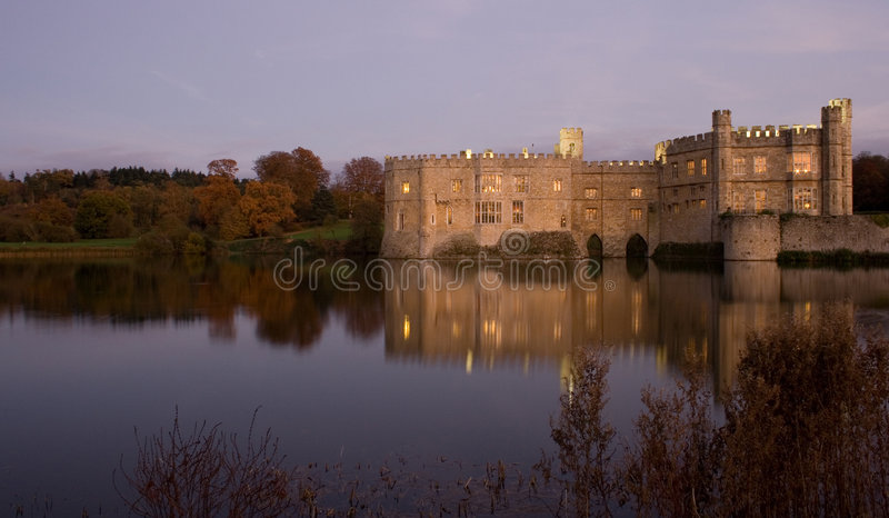 Old English Castle and lake at sunset stock photo