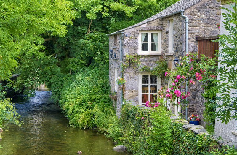 Old English cottage on river. An old, quaint English cottage on the bank of a small river in Cartmel, England stock image