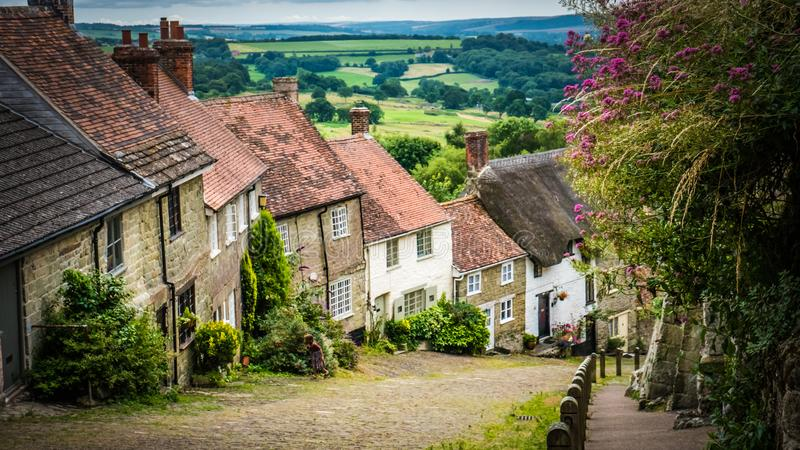 Cobbled street Gold Hill with traditional cottages in Shaftesbury, UK. Old English limestone houses with thatched roofs with green fields countryside in the stock photography