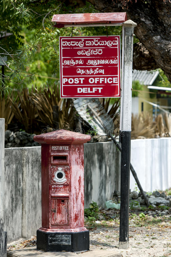 The old English post box outside the modern post office on Delft Island in the Jaffna region of Sri Lanka. The old English post box painted royal red outside stock photos