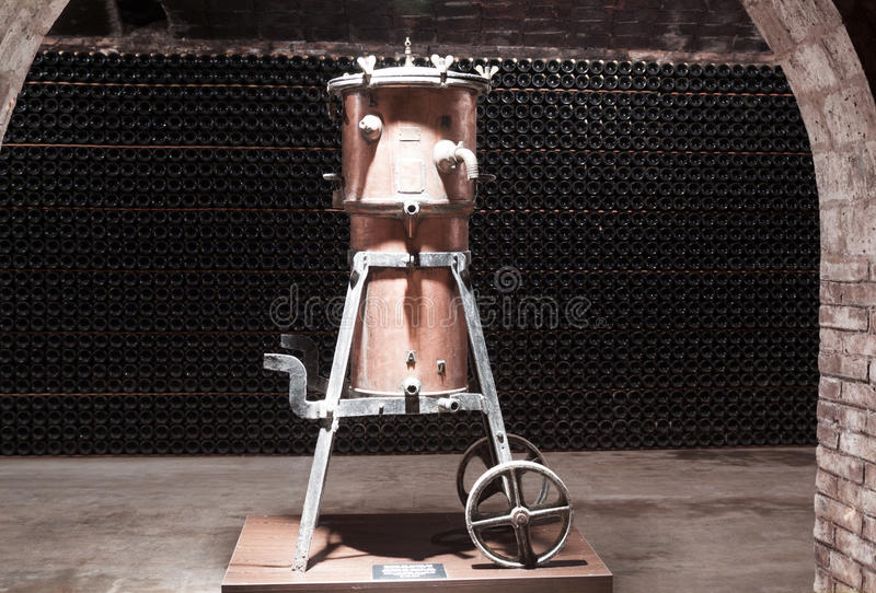 Old equipment for the production of wine. In the warehouse on the background of rows of bottles stock images
