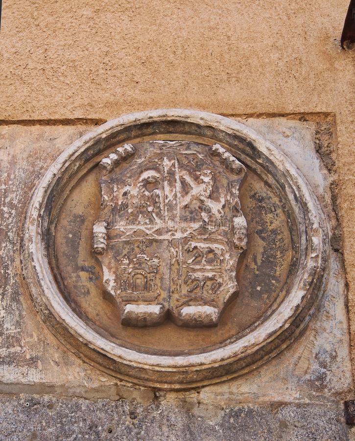 Old Stone Heraldic Shield, Segovia, Spain. An old and eroded and worn stone heraldic shield or coat of arms, mounted on the exterior wall of an historic Segovia royalty free stock images