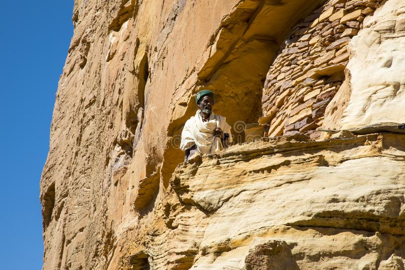 Abuna Yemata Guh, Tigray rock hewn churches. Gheralta massif. Old Ethiopian man standing at the entrance of the Abuna Yemata Guh rock hewn church in Tigray royalty free stock photography