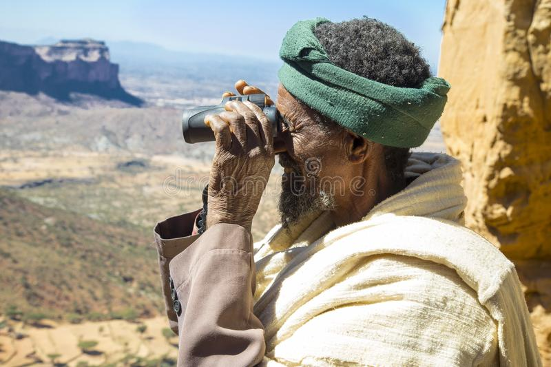 Abuna Yemata Guh, Tigray rock hewn churches. Gheralta massif. Old Ethiopian man standing at the entrance of the baptism section of the Abuna Yemata Guh rock hewn royalty free stock images