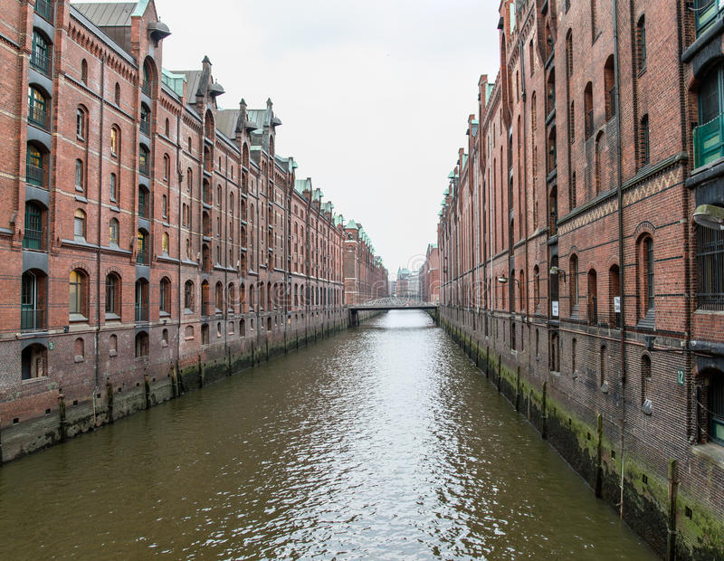 Old European building along waterway. Old European residential buildings on both sides of a wide waterway or canal receding into the horizon stock photo