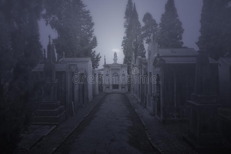Cemetery street in a foggy night. Old european cemetery street in a creepy foggy full moon night stock photo