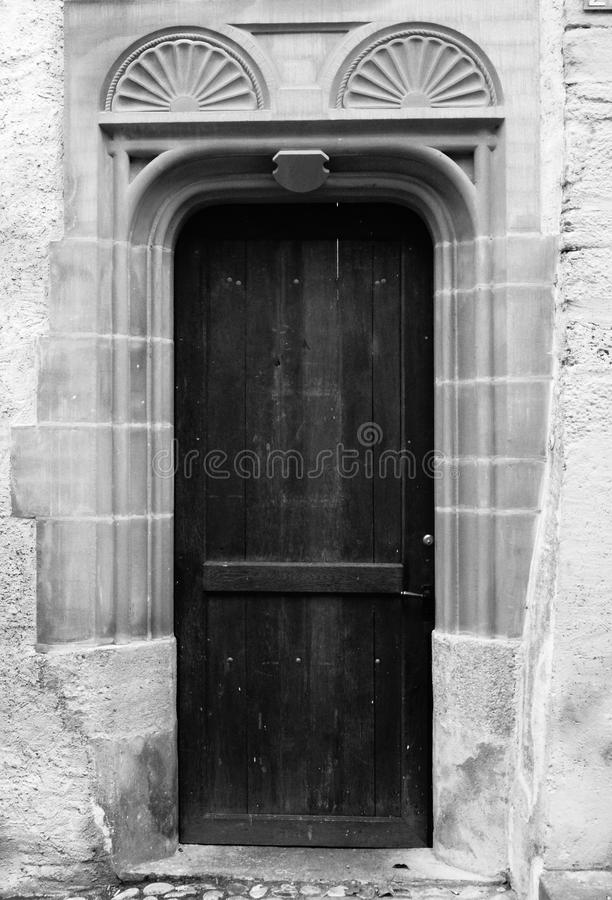 A black and white image of a very old door with a double half sunburst above the doorframe carved in stone with a decorative shield. & Old European Door Double Sunburst Stock Image - Image of black ...