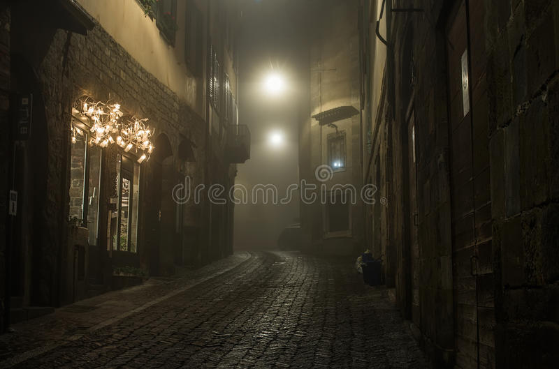 Old European narrow empty street of medieval town on a foggy evening. Taken in Bergamo, Citta Alta, Lombardia stock photography