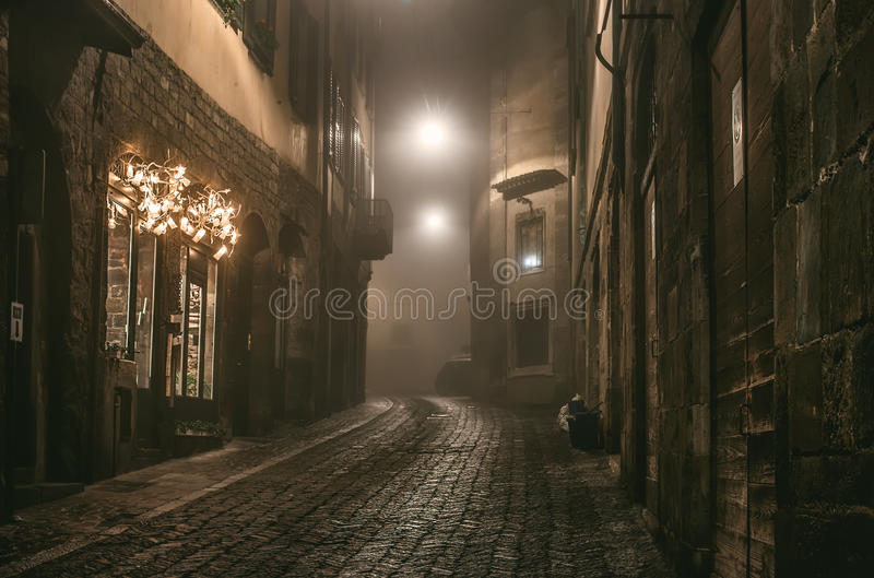 Old European narrow empty street of medieval town on a foggy evening. Taken in Bergamo, Citta Alta, Lombardia. Old European narrow empty street of a medieval stock photography