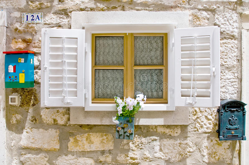 Old European window with shutters,. Old styled European window with shutters, flower box and mail box stock photo