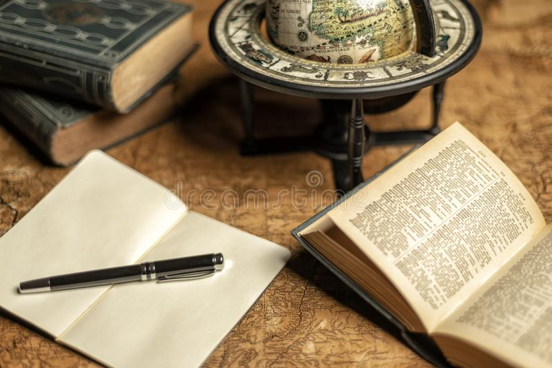 Old expedition map with notebook. books and globe stock photo