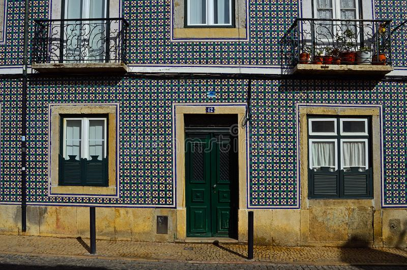 The old facade of the building is covered with azulejo. Ceramic tile. Cordoeiros Street 42, Lisbon, Portugal. November 02, 2018 Editorial photography stock photography