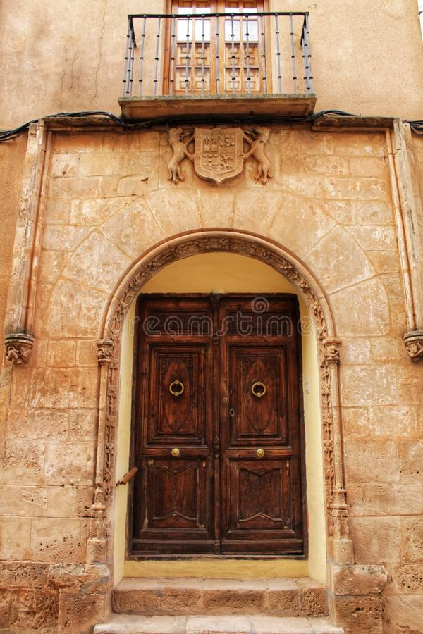 Old facade and entrance of majestic house in Alcaraz, Albacete province, Spain. Old stone facade made of carved stone and vintage wooden door in a majestic house stock image