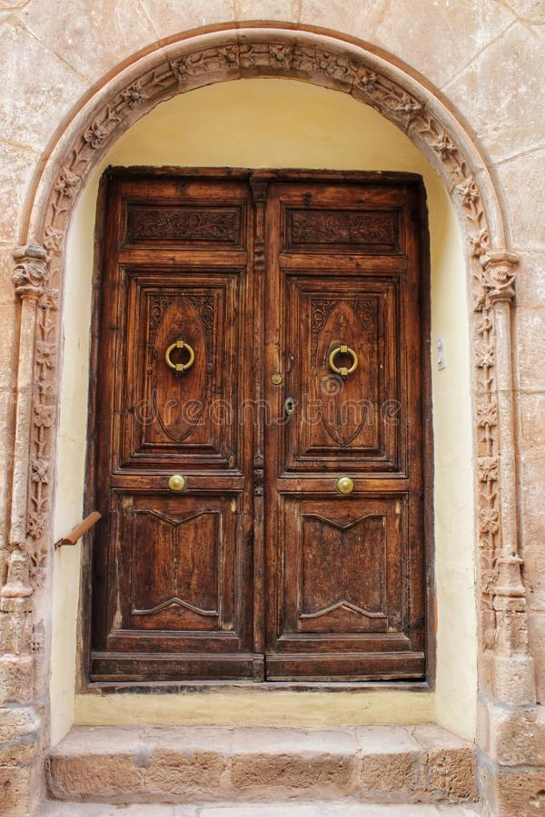 Old facade and entrance of majestic house in Alcaraz, Albacete province, Spain. Old stone facade made of carved stone and vintage wooden door in a majestic house royalty free stock photography
