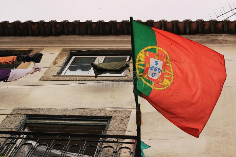 Old facade of typical Lisbon house with Portugal flag. Old facade of typical Lisbon house with a Portugal flag and hanging clothes in clothesline stock photo