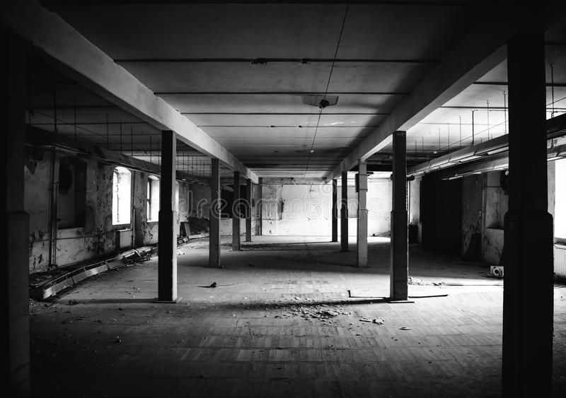 Old factory floor II. A dark scary abandoned factory floor in black and white royalty free stock photo