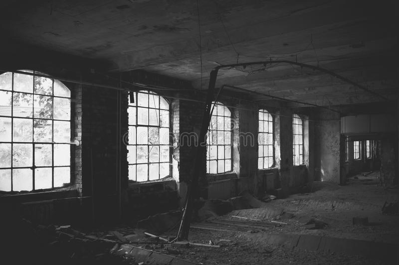 Old factory floor III. A dark scary abandoned factory floor in black and white royalty free stock photography