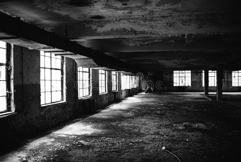 Old factory floor IV. A dark scary abandoned factory floor in black and white royalty free stock photography