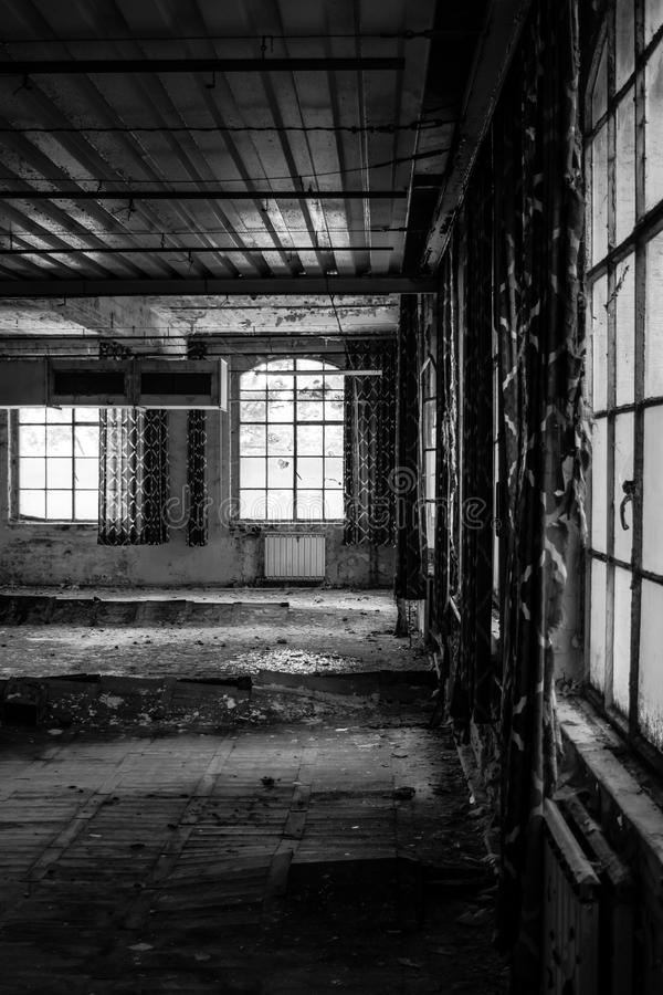 Old factory floor V. A dark scary abandoned factory floor in black and white royalty free stock photography