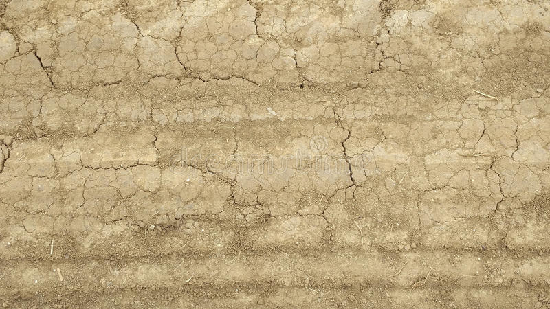 Old faded dirt road. Dusty dry cracked earth. Old faded dirt road. Car trails at the bottom stock image