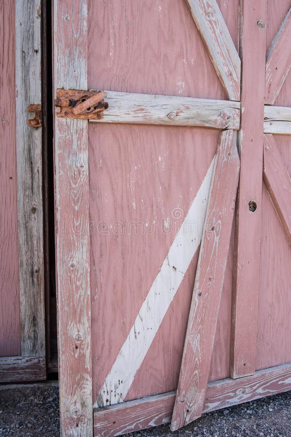 Old Faded red barn being painted. Faded red old barn peeling paint needs work  white being  painted roller bright refresh redo remodel open door handle broken royalty free stock photo