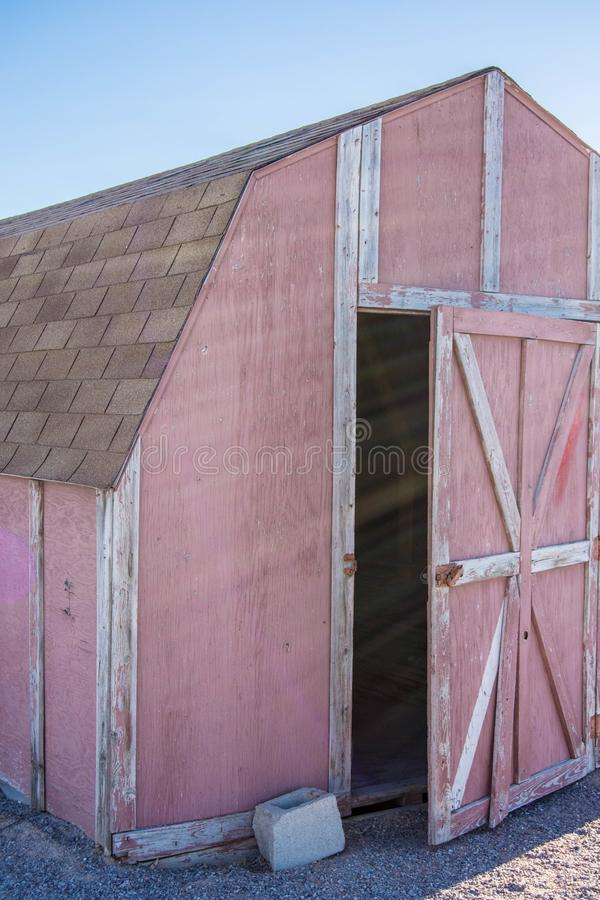 Old Faded red barn with peeling paint. Faded red old barn peeling paint needs work  white stock photo