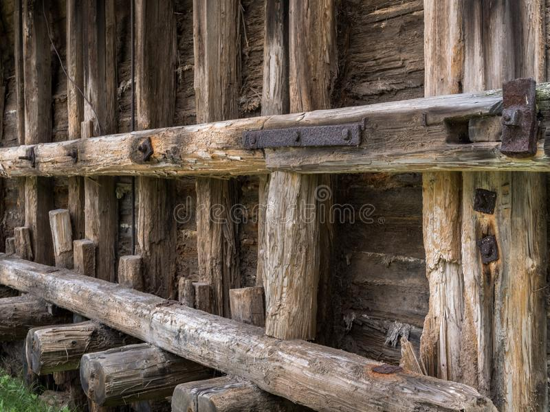Old faded scratched beams of a historic building with rusty steel elements. Elements of an ancient structure made of wooden logs and steel bolts stock photography