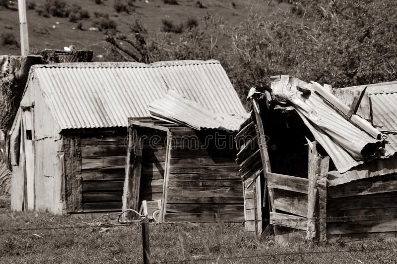 Old falling down rustic farm sheds in sepia toned image stock photography