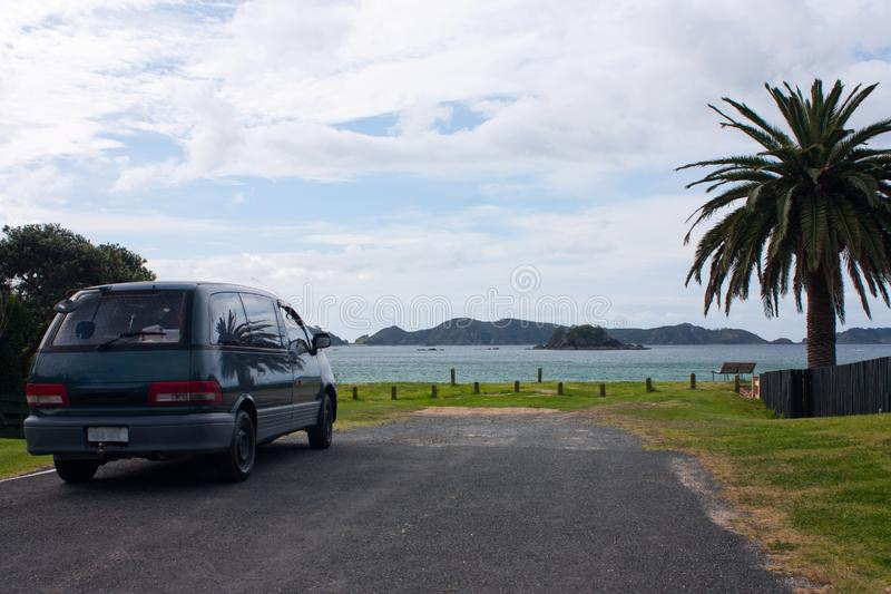 An old family car / backpacker van parked by the sea on a tarmac road, a palm tree on the right, in Northland in New Zealand. An old family car / backpacker van royalty free stock photo