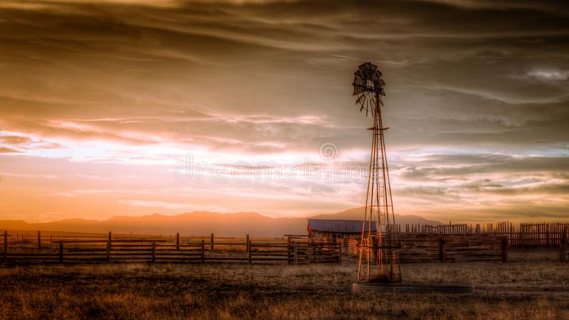 Old Farm in the Country. An old farm and cattle ranch in the country during sunset. There is a tall windmill stock photos
