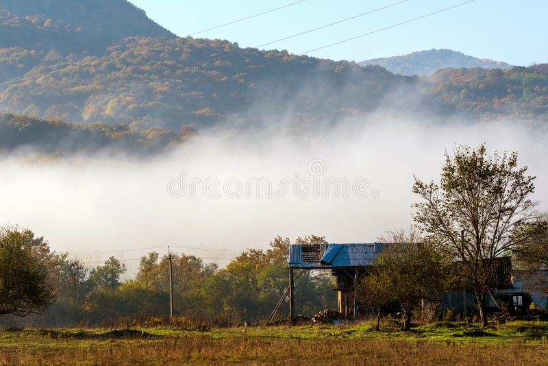 Old farm house in mountain in autumn foggy morning. Mountain village and old farm in the mountains. Clouds of fog and sky at back royalty free stock photos