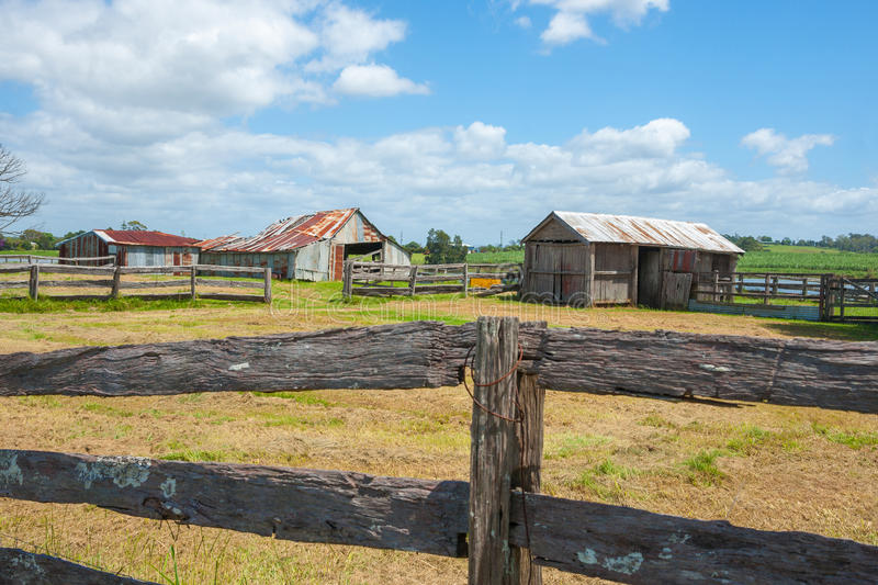 Old farm sheds beyond post and rail fences in rustic rural scene. From road in country Australia between Ulmarra and Yamba stock images
