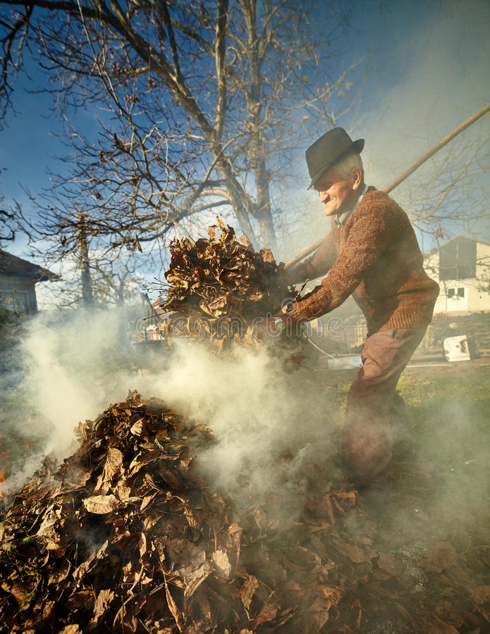 Free Old Farmer Burning Dead Leaves Royalty Free Stock Images - 47316779