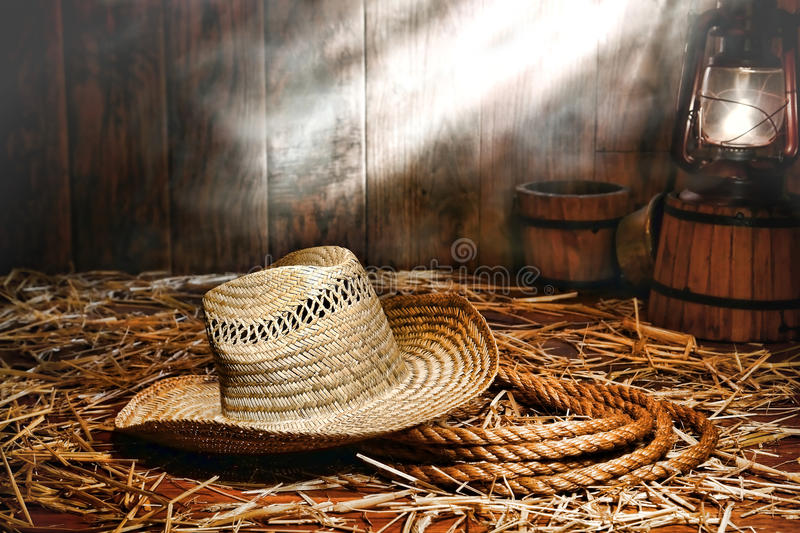 Old Farmer Hat and Ranching Rope in Antique Barn. Old farmer straw hat over a sisal ranching rope on wood floor covered with loose hay lit by an antique kerosene stock photos