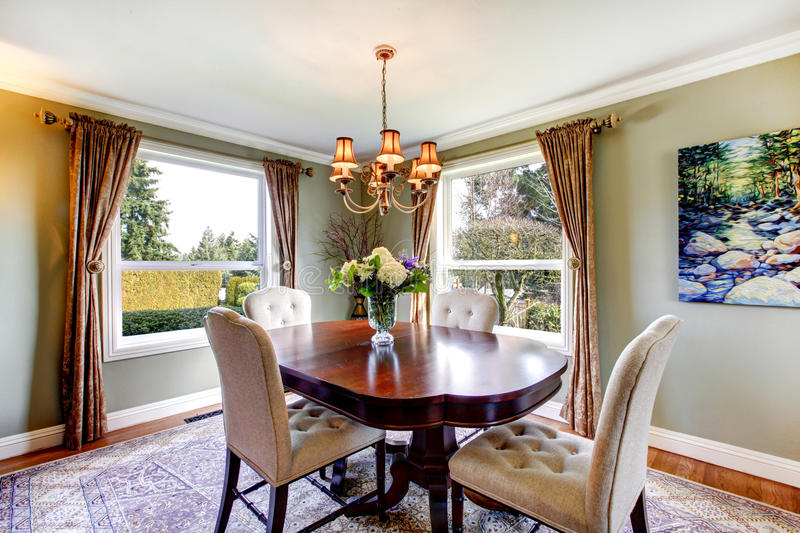 Old-fashined design of a dining room. Olive tones dining room with old-fashined dining table set, chandelier, curtains and carpet royalty free stock image