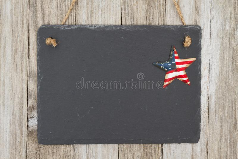 Old fashion patriotic hanging chalkboard background. A retro chalkboard with a vintage USA star hanging on weathered wood background with copy space for your royalty free stock images